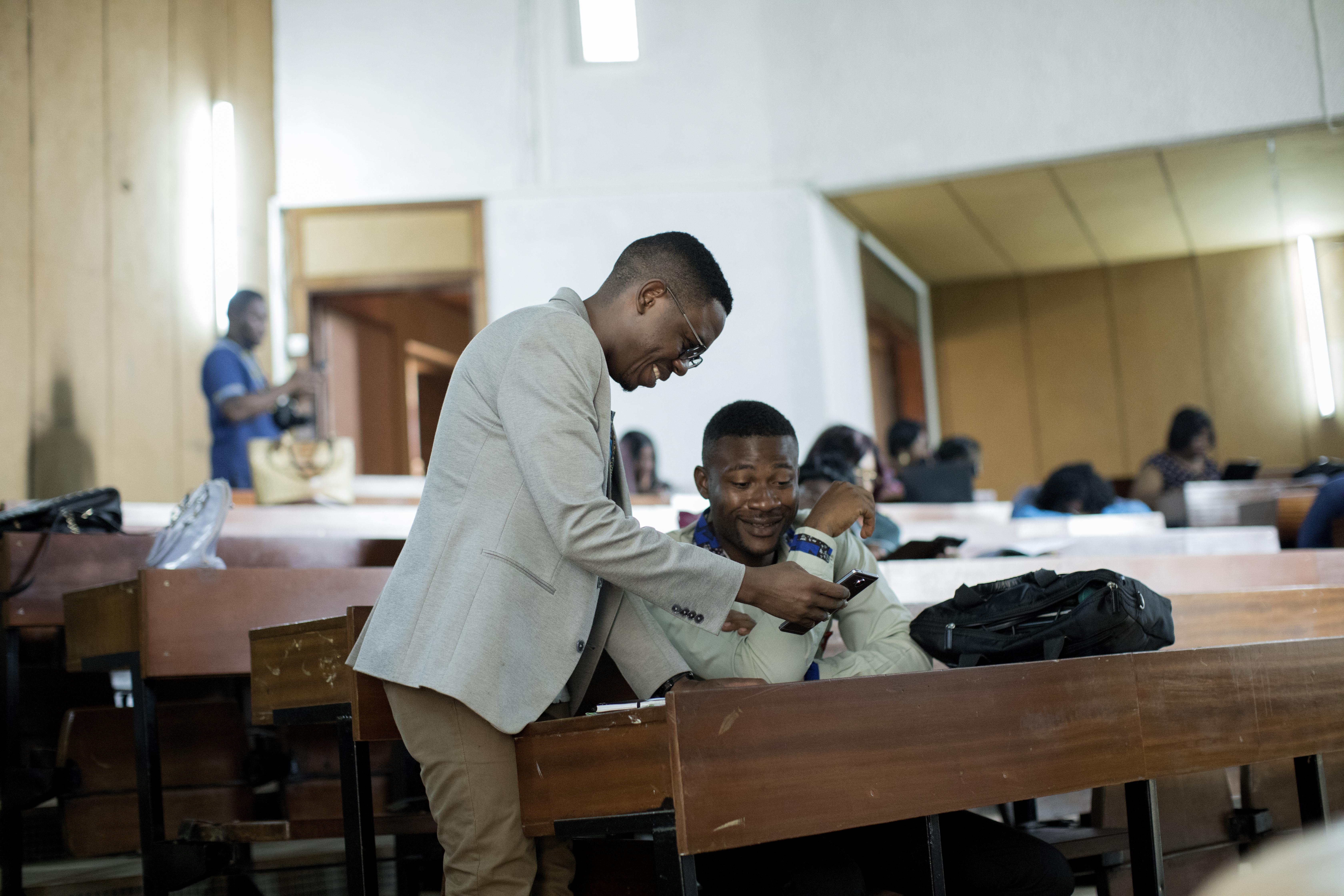 Serge travaille chez Affirmative Action, une ONG qui s'emploie à sensibiliser les communautés LGBTQ au VIH. Joseph Messinga, responsable des communications chez Affirmative Action discute de l'horaire de la journée avec Serge au lendemain d'une conférence où ce dernier était l'un des panélistes conversant des problèmes auxquels sont confrontées les communautés LGBTQ au Cameroun.
